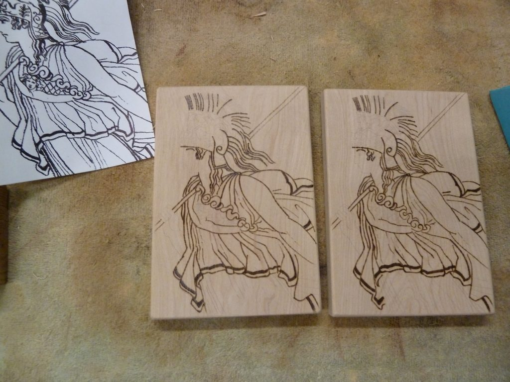 The image of Athena burned into both pieces of wood.