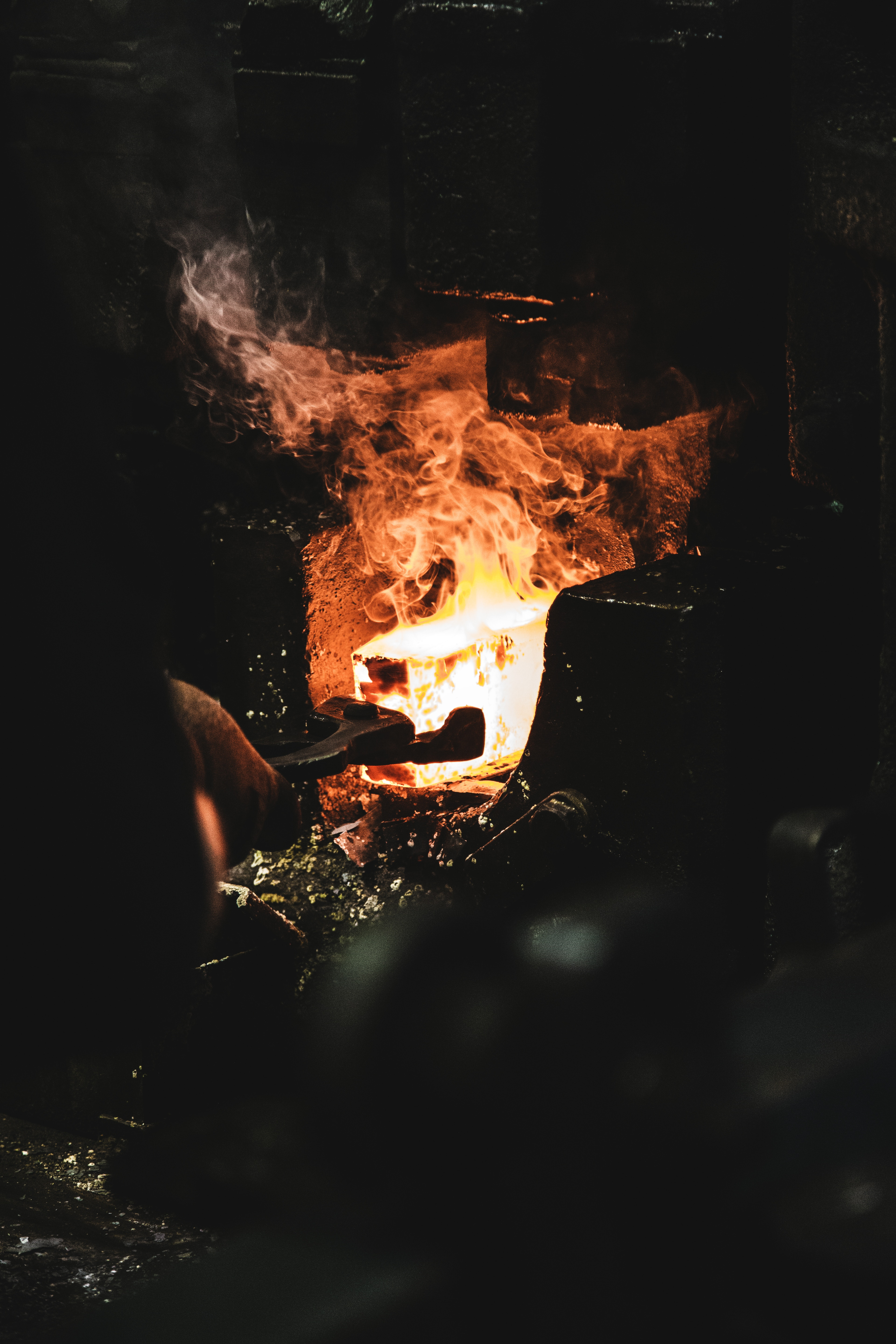 A person melting iron in a forge