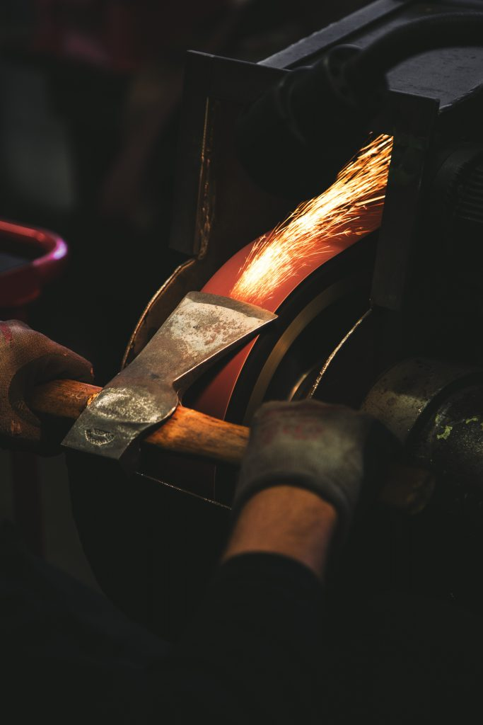Sparks fly as someone sharpens an axe blade on a wheel